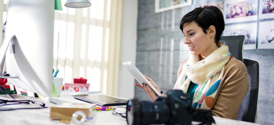 woman-with-scarf-sitting-at-desk-searching-for-something-on-her-tablet